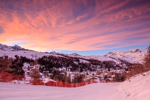Pink clouds at sunset on the alpine village of Madesimo and the snowy ski slopes, Spluga Valley, Valの写真素材 [FYI03784519]