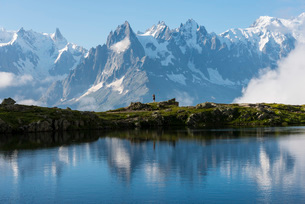 Hikers reflected in Lake Cheserys, Mont Blanc, French Alps, France, Europeの写真素材 [FYI03784688]