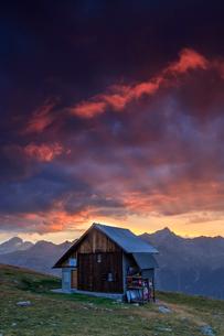 Wooden hut under fiery sky and clouds at sunset, Muottas Muragl, St. Moritz, Canton of Graubunden, Eの写真素材 [FYI03784726]