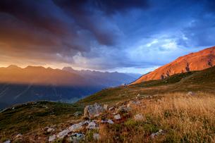 Fiery sky and dark clouds on high peaks of Muottas Muragl at sunset, St. Moritz, Canton of Graubundeの写真素材 [FYI03784740]