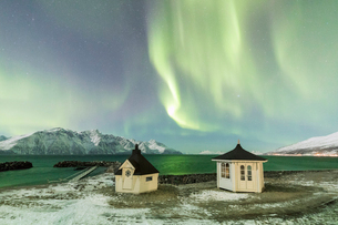 The Northern Lights (aurora borealis) and stars illuminate the wooden huts by icy sea, Djupvik, Lyngの写真素材 [FYI03784797]