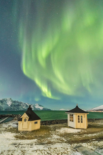 The Northern Lights (aurora borealis) and stars illuminate the wooden huts by icy sea, Djupvik, Lyngの写真素材 [FYI03784801]