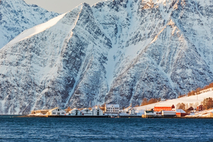 The typical fishing village of Hamnes framed by snowy peaks and the cold sea, Lyngen Alps, Troms, Noの写真素材 [FYI03784810]