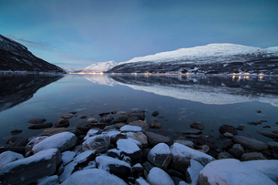 Snowy peaks reflected in the cold sea at dusk, Manndalen, Kafjord, Lyngen Alps, Troms, Norway, Scandの写真素材 [FYI03784814]