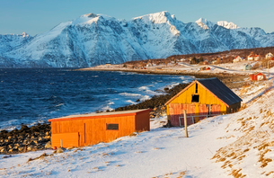 Typical wooden huts called Rorbu surrounded by waves of the cold sea and snowy peaks, Djupvik, Lyngeの写真素材 [FYI03784820]