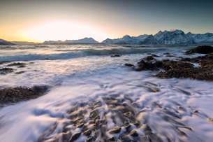 The sunset light reflected on the waves of cold sea crashing on the rocks, Djupvik, Lyngen Alps, Troの写真素材 [FYI03784822]