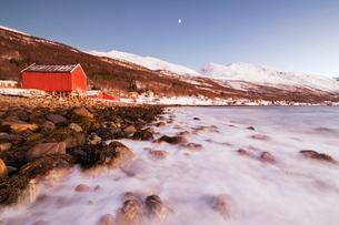 Waves of cold sea crashing on the rocks and typical wooden huts called Rorbu, Djupvik, Lyngen Alps,の写真素材 [FYI03784824]