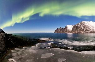 Panorama of frozen sea and rocky peaks illuminated by the Northern Lights (aurora borealis), Tungeneの写真素材 [FYI03784829]