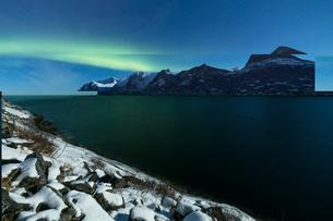 Northern Lights and stars over Senjahopen peak surrounded by the frozen sea, Senja, Mefjordbotn, Troの写真素材 [FYI03784906]