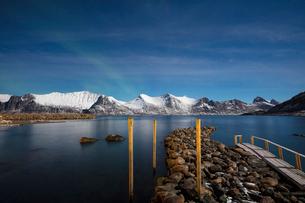 Stars of the polar night frame the frozen sea surrounded by snowy peaks, Mefjord Berg, Senja, Tromsの写真素材 [FYI03784914]