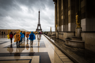 Heading towards the Eiffel Tower, tourists brave the rain in colourful ponchos at the Palais De Chaiの写真素材 [FYI03785013]