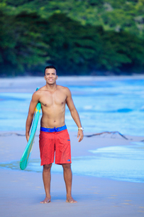 Brazilian male surfer with a Brazilian flag surfboard on a beach in Rio de Janeiro state, Brazil, Soの写真素材 [FYI03785387]