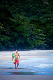 Brazilian male surfer with a Brazilian flag surfboard on a beach in Rio de Janeiro state, Brazil, Soの写真素材 [FYI03785394]