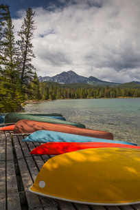 Colourful canoes and kayaks on the bank of Annette Lake with Pyramid Mountain in the background, Jasの写真素材 [FYI03785587]
