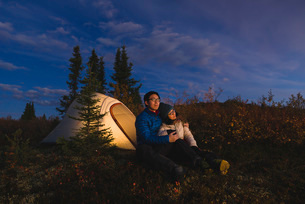 Couple sitting in front of an illuminated tent, Alaska, United States of America, North Americaの写真素材 [FYI03785763]