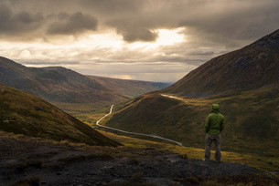 Lone hiker looking at mountain landscape at sunset, Alaska, United States of America, North Americaの写真素材 [FYI03785770]