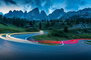 Car trail lights on Passo Pordoi with mountain backdrop at dusk, Province of Bolzano, South Tyrol, Iの写真素材 [FYI03786048]