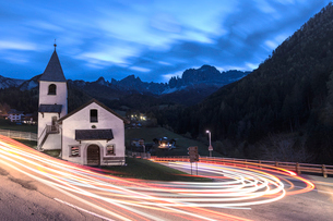 Lights of car trails around the Church of San Cipriano, Tires Valley, Dolomites, South Tyrol, Bolzanの写真素材 [FYI03786394]