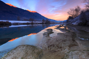 The colors of sunset are reflected in the Adda River, Valtellina, Lombardy, Italy, Europeの写真素材 [FYI03786899]