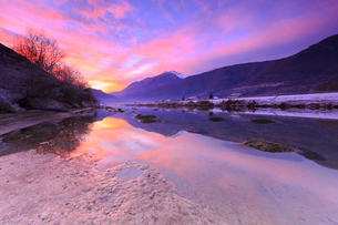 The colors of sunset are reflected in the Adda River, Valtellina, Lombardy, Italy, Europeの写真素材 [FYI03786902]