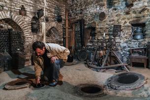 Sampling wine from underground vats, Nodari Wine Cellar, Velistsikhe, near Sighnaghi, Kakheti, Georgの写真素材 [FYI03786940]