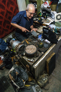 Armenian shoe repairer at work in his shop on Jerusalem Street, Old Town, Tbilisi, Georgia, Centralの写真素材 [FYI03786946]