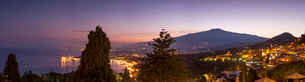 Panoramic view of Mount Etna and Giardini Naxos at dusk from Taormina, Sicily, Italy, Mediterranean,の写真素材 [FYI03786950]