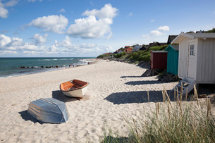 Boats and beach huts on white sand beach with town behind, Tisvilde, Kattegat Coast, Zealand, Denmarの写真素材 [FYI03787277]