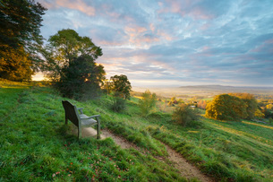 Cotswold Way path and bench with views to the Malvern Hills at sunset, Ford, Cotswolds, Gloucestershの写真素材 [FYI03787285]