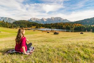 Woman sitting and staring at Gerold lake and Karwendel Alps, Krun, Upper Bavaria, Bavaria, Germany,の写真素材 [FYI03787753]