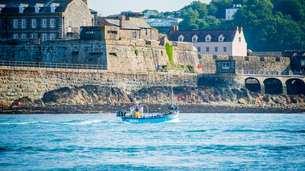 Traditional Guernsey crab and lobster boat coming into St. Peter Port Harbour, passing Castle Cornetの写真素材 [FYI03788253]