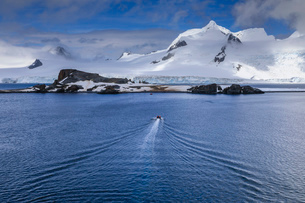 Tourists on a zodiac boat approach Half Moon Island, Livingston Island mountain backdrop, South Shetの写真素材 [FYI03788364]