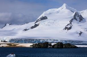Tourists on a zodiac boat approach Half Moon Island, Livingston Island mountain backdrop, South Shetの写真素材 [FYI03788365]