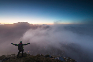 Hiker on top of Monte Coltignone at dawn, province of Lecco, Lombardy, Italy, Europeの写真素材 [FYI03788461]
