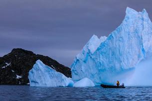 Person in zodiac looks at a huge blue iceberg, near Torgersen Island, Anvers Island, Antarctic Peninの写真素材 [FYI03788787]