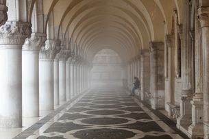 Misty view of pillars with lone woman sitting, Doge's Palace, St. Mark's Square, Venice, UNESCO Worlの写真素材 [FYI03788799]