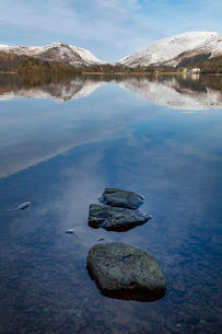 Stones in shallow water and perfect reflection of snow covered mountains and sky in the still watersの写真素材 [FYI03788936]