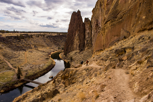 Two hikers descend a path to the river by some large rock formations, Oregon, United States of Ameriの写真素材 [FYI03788979]
