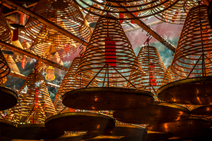 Beams of light streaming into Man Mo Temple past the large incense coils hanging from the ceiling ofの写真素材 [FYI03789008]