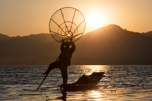 A fisherman standing on one leg and holding his fishing net at sunset on Inle Lake, Shan State, Myanの写真素材 [FYI03789011]