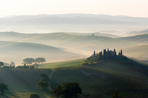 Podere Belvedere and misty hills at sunrise, Val d'Orcia, San Quirico d'Orcia, UNESCO World Heritageの写真素材 [FYI03789028]
