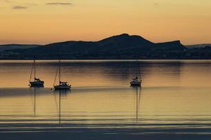 Sailboats at sunrise in Aberdour with Edinburgh in the background, Fife, Scotland, United Kingdom, Eの写真素材 [FYI03789056]