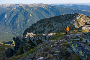 A hiker climbs along a high ridge near Maliovitsa in the Rila Mountains with distant views of valleyの写真素材 [FYI03789195]