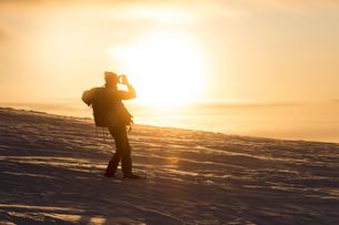 Photographer at sunset, Pallas-Yllastunturi National Park, Muonio, Lapland, Finland, Europeの写真素材 [FYI03789292]
