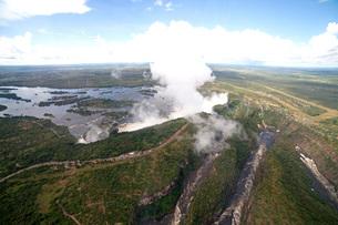 Mist rises above the Victoria Falls waterfall (Mosi-oa-Tunya), UNESCO World Heritage Site on the borの写真素材 [FYI03789649]