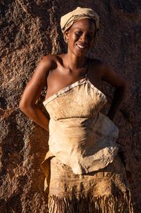 Portrait of woman resting against a rock in the sun at a Damara tribal village near Twyfelfontein, Nの写真素材 [FYI03789731]