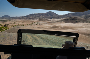 View over Hoarusib Riverbed from inside a safari vehicle, mountain range in background, Puros, northの写真素材 [FYI03789733]