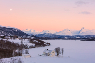Sunrise on typical house with Lyngen Alps in the background, Mestervik, Troms county, Norway, Scandiの写真素材 [FYI03790242]