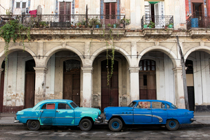 Two blue cars face nose to nose outside a dilapidated building, Havana, Cuba, West Indies, Caribbeanの写真素材 [FYI03790254]