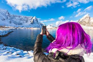 Woman with fuchsia hair taking photo with smartphone, Reine Bay, Lofoten Islands, Nordland, Norway,の写真素材 [FYI03790301]